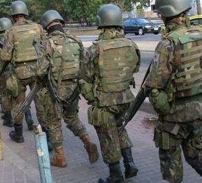 Exército brasileiro caminha em fila única pelas ruas do morro da Rocinha